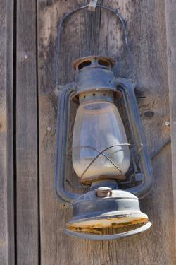 Lamp hanging on wooden wall by Darrell Gulin