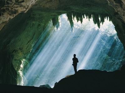 A Man Stands Below the Mouth of a Giant Cave
