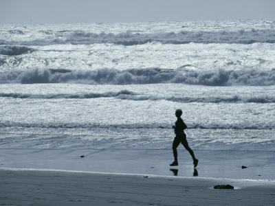 A Person Jogs Along the Beach