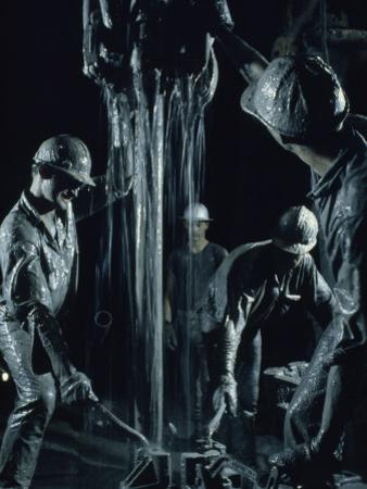 Oilmen Covered in Mud Pull Up a Drill Pipe to Change the Bit