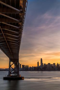 Bay Bridge from Treasure Island at sunset with colorful clouds over San Francisco skyline by David Chang