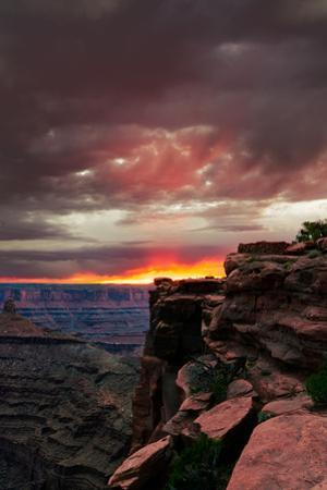 Red sunset with moody clouds and red rock canyons in Dead Horse Point State Park near Moab, Utah by David Chang