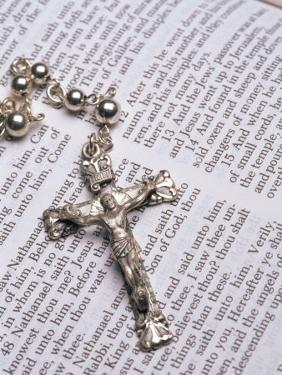 Silver Crucifix Lying on Open Bible by David Davis