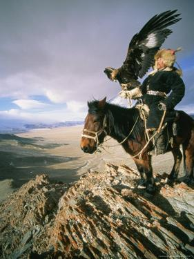 Hunter on Horseback Atop a Hill Holding a Golden Eagle in Mongolia by David Edwards