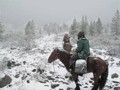 Two Horsemen Riding in a Late Summer Snow Storm in Western Mongolia
