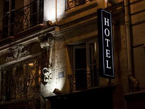 A Sign Outside a Hotel in Paris at Night by David Evans