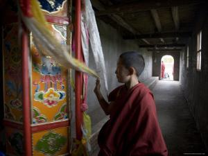 Young Monk Spinning a Prayer Wheel with Flags in a Monastery, Qinghai, China by David Evans