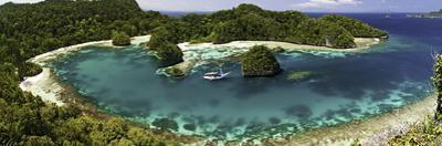 Bugis Schooner Dive Vessel at Anchor in a Limestone Island Lagoon, Uranie Island by David Fleetham