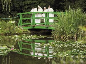 Four Nuns Standing on the Japanese Bridge in the Garden of the Impressionist Painter Claude Monet by David Hughes