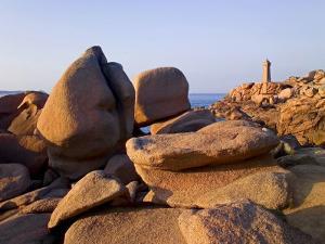 Sunset Over Rocks and Lighthouse at Pars-Kamor, Ploumanach, Breton Corniche, Cotes d'Armor by David Hughes