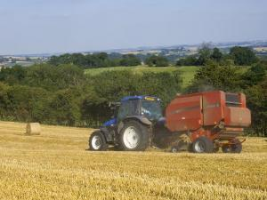 Tractor Collecting Hay Bales at Harvest Time, the Coltswolds, England by David Hughes