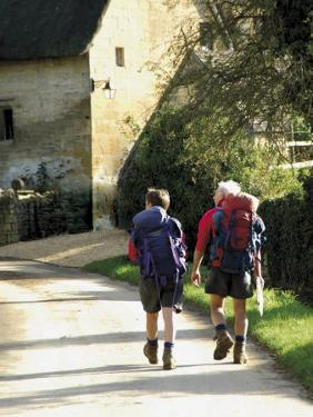 Two Walkers with Rucksacks on the Cotswold Way Footpath, Stanton Village, the Cotswolds, England by David Hughes