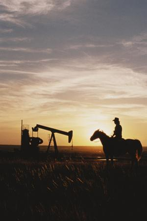 Old West, New West, Man Sitting on Horse with Oil Refinery at Sunset