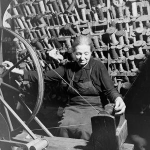 Old Lady at a Time Worn Wheel Winding Strands for Tapestries at Aubusson, France June 1946 by David Scherman