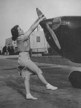 Woman Turning Propeller to Start Plane by David Scherman