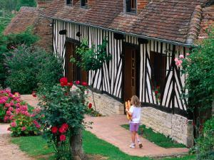 Child with Baguettes in Front of Half-Timbered Cottage by David Tomlinson
