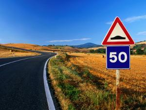 Speed Sign on Winding Road Near San Quirico d'Orica, Tuscany, Italy by David Tomlinson