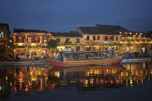 Boat and restaurants reflected in Thu Bon River at dusk, Hoi An, Vietnam by David Wall