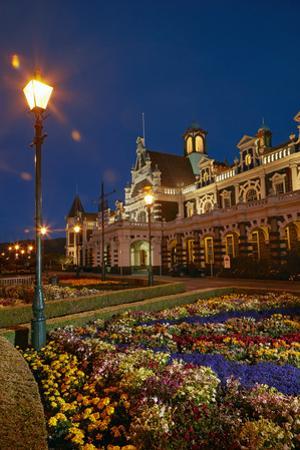 Flower garden and historic Railway Station at night, Dunedin, South Island, New Zealand by David Wall