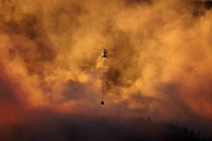 Smokey sunset and helicopter fighting fire at Burnside, Dunedin, South Island, New Zealand by David Wall