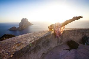 A Young Woman Does an Acrobatic Yoga Pose at the Torre Des Savinar Lookout Tower in Sw Ibiza by Day's Edge Productions