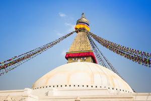 Bodhnath Stupa with Buddha Eyes and Prayer Flags, Clear Blue Sky, Kathmandu, Nepal. Stock Photo: by De Visu