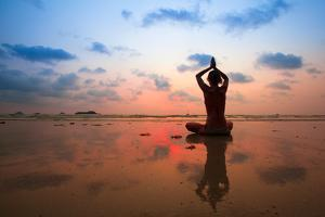Silhouette Young Woman Practicing Yoga On The Beach At Sunset by De Visu