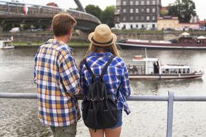 Young Couple on a Journey to Europe, Standing on the Bank of the Vistula, Rear View. by De Visu