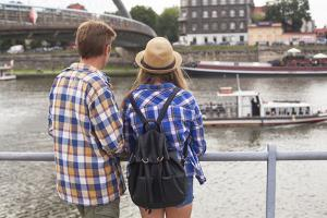 Young Couple on the River Bank in a European City (Rear View) Romantic Journey. by De Visu