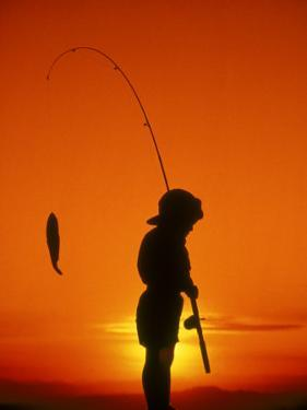 Silhouette of Boy Fishing at Sunset by Dean Berry