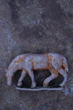Battered Lead Model of Grazing Horse Lying on Tarnished Metal by Den Reader