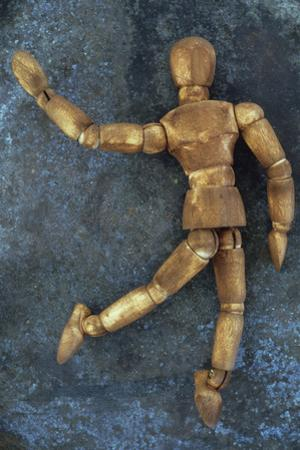 Dark Stained Wooden Mannequin Lying by Den Reader