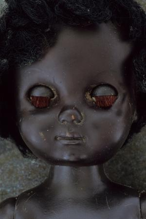 Head and Shoulders of Modern Plastic Black Girl Doll Slightly Scratched and Soiled Lying by Den Reader