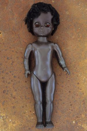 Modern Plastic Black Girl Doll Slightly Scratched and Soiled Lying on Rusty Metal Sheet by Den Reader