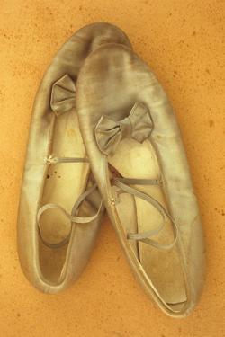 Pair of Ballet or Dancing Shoes Once White But Now Used and Grubby Sitting One Face Down by Den Reader