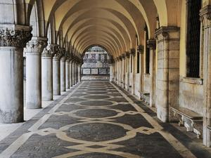 Columns and Archways Along Patterned Passageway at the Doge's Palace, Venice, Italy by Dennis Flaherty