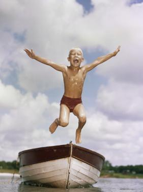 Boy Jumping Off Bow of Boat into Water by Dennis Hallinan