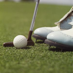 Close Up of Golf Ball , Putter and Shoes on Grass by Dennis Hallinan
