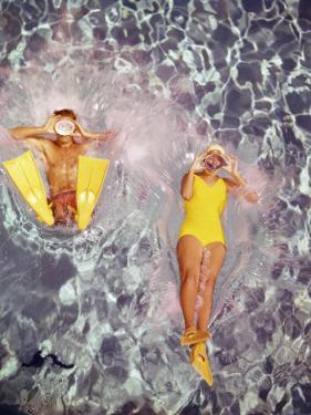 Couple Diving in Swimming Pool by Dennis Hallinan