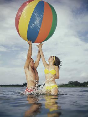 Couple Jumping in Water Reaching for Large Beach Ball by Dennis Hallinan
