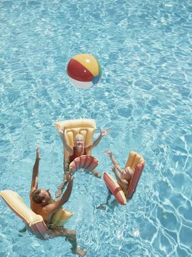 Family Tossing Beach Ball While Floating on Pool Rafts by Dennis Hallinan
