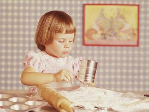 Girl Sifting Flour for Cupcakes by Dennis Hallinan