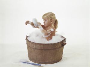 Girl Taking a Bubble Bath in Wooden Bucket by Dennis Hallinan