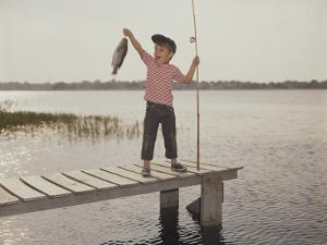 Happy Boy on Dock with Freshly Caught Fish by Dennis Hallinan