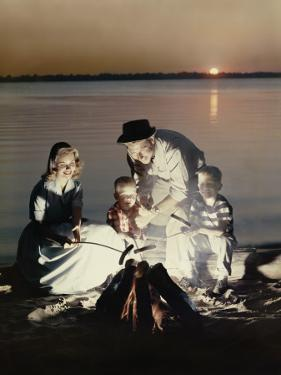 Happy Retro Family Roasting Hot Dogs over Fire by Dennis Hallinan
