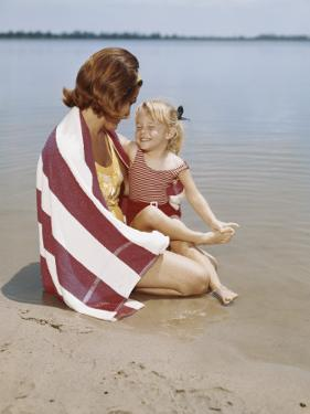Retro Mother and Daughter Lying Down on Lakeshore by Dennis Hallinan