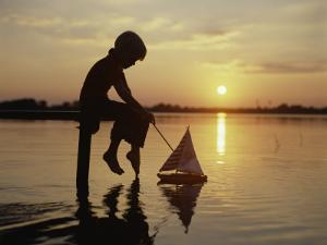 Silhouette of Boy Sitting at Pier with Toy Sailboat by Dennis Hallinan