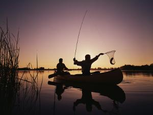 Two Men Catching Fish in Canoe at Sunset by Dennis Hallinan