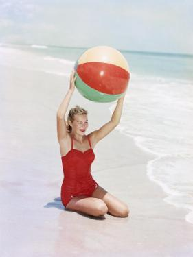 Woman Sitting with Beach Ball by Ocean by Dennis Hallinan