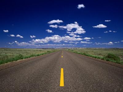 Road Leading to Horizon Beneath Blue Sky, USA by Dennis Johnson